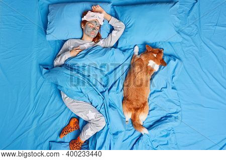 Serene Relaxed European Woman Sleeps Peacefully Lies In Favorite Pose On Bed Applies Clay Beauty Mas
