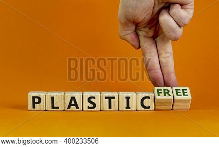 Plastic Free Symbol. Male Hand Turns Cubes With Words 'plastic Free'. Beautiful Orange Background. B