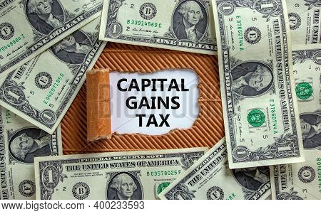 Capital Gains Tax Symbol. The Text 'capital Gains Tax' Appearing Behind Torn Brown Paper. Dollar Bil