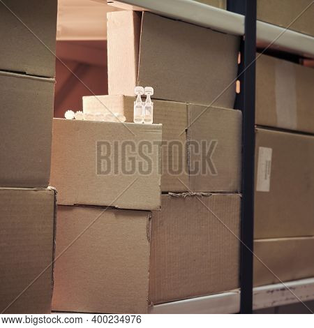 Coronavirus Vaccine In Boxes In The Warehouse. Virus Vaccination Problems And Insufficient Medicatio