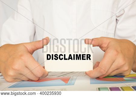 A Man In The Office Holds A Card With Text Disclaimer . Business Concept