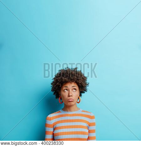 Vertical Shot Of Unhappy Dark Skinned Woman Looks With Gloomy Discontent Face Expression Upwards Fee