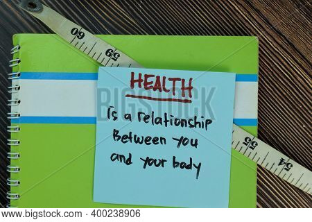 Health Is A Relationship Between You And Your Body Write On Sticky Notes Isolated On Wooden Table. M