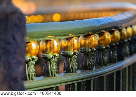 Gilded Elements Of The Vintage Forged Railings Of The Bridge. Shallow Depth Of Field With Blur