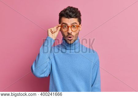 Waist Up Shot Of Surprised European Man Keeps Hand On Spectacles Looks With Great Wonder At Camera S