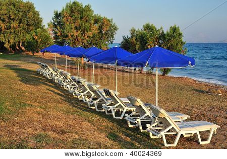 Beach With Blue Parasols