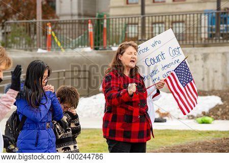 Helena, Montana / Nov 7, 2020: White Women And Children Praying Raising Hand At Donald Trump's Stop