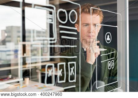 Young pensive male software developer keeping hand by chin while standing in front of noticeboard and looking at sketches of mobile app