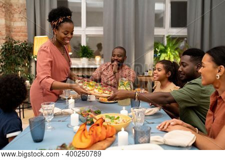 Happy young African woman putting appetizing vegetarian sandwiches for big family on festive table while her son or nephew helping her