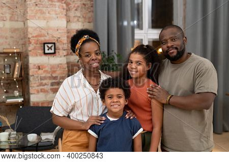 Happy young African couple and their affectionate son and daughter standing close to each other in front of camera in living-room