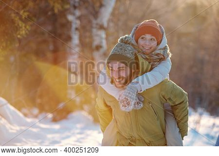 Cheerful guy in winterwear giving his happy girlfriend piggyback while moving along forest and enjoying weekend in natural environment