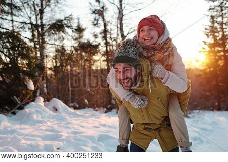 Joyful guy in winterwear giving his happy girlfriend piggyback while chilling out in forest and enjoying winter weekend in natural environment