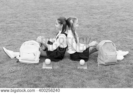 Come, Relax And Enjoy. School Girls Sit On Green Grass. Happy Girls Wear School Uniform. Back To Sch