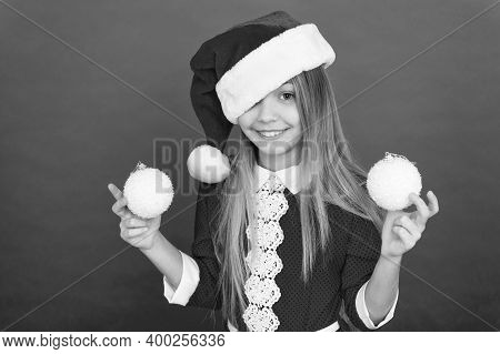 Im On Santa Good List. Happy Child Hold Xmas Tree Balls. Small Girl Smile With Santa Look. Celebrate