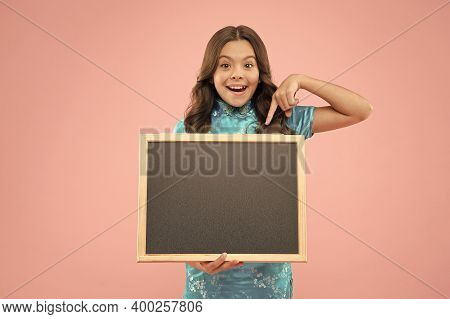 For Your Text. Blackboard For Advertising Text, Copy Space. Happy Girl Hold Blackboard Pink Backgrou
