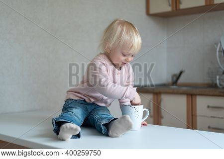 Two-year-old Child In The Kitchen With Cup In His Hands. Portrait Of Blonde Toddler In The Kitchen.