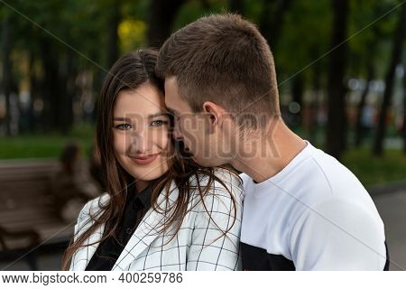 Portrait Of Beautiful Young Couple In Park. Guy Gently Touches The Girls Cheek With His Nose