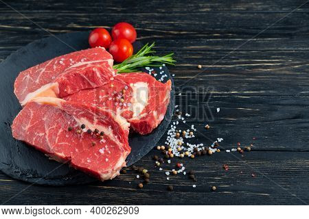 Three Pieces Of Juicy Raw Beef With Rosemary On A Stone Cutting Board On A Black Wooden Table Backgr