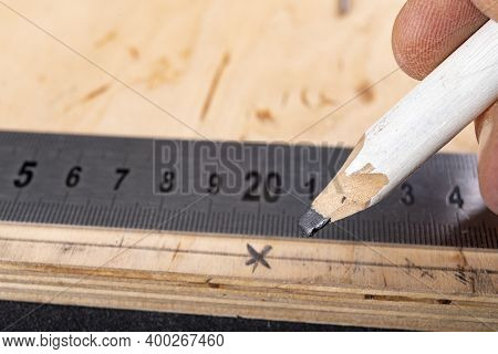 Metal Measuring Tape And Pencil For Drawing On Wood. Minor Carpentry Work In The Workshop.