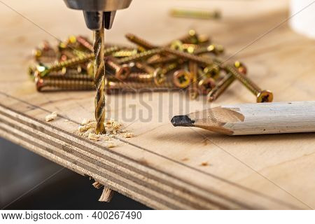 Drilling Holes In Plywood With A Screwdriver. Minor Carpentry Work In The Workshop.