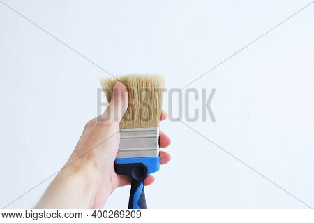 Paint Brush In Hand. He Touches The Bristles Of The Brush With His Finger.