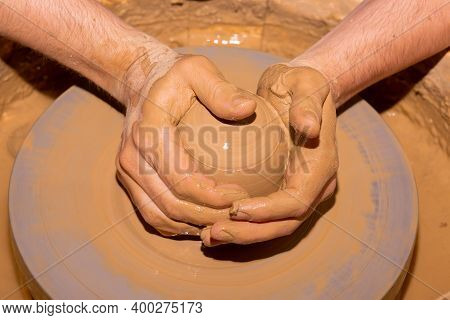 Cropped Closeup Image Of Unrecognizable Male Hands Ceramics Maker Working With Pottery Wheel In Cozy