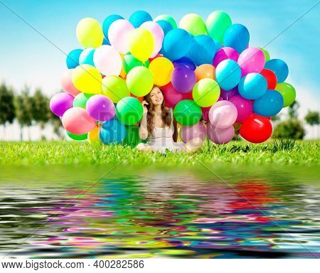 Happy birthday girl with balloons jumping near the water. Holiday and joy for a woman