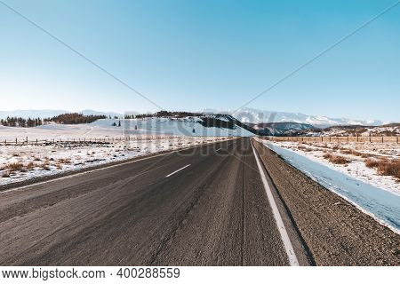 Scenic View Of Empty Road With Snow Covered Landscape In Winter Season.
