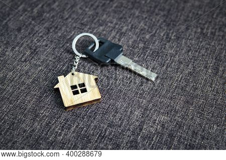 Close Up Of Key With House-shaped Key Ring At Dark Sackcloth Background. Concept Of Purchasing Livin