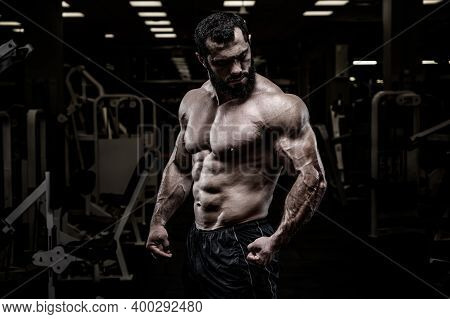 Strong Young Bearded Caucasian Male With Sport Physique Body Standing In Dark Fitness Gym With Equip