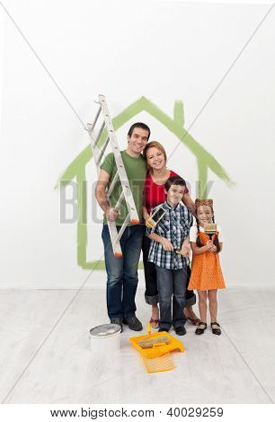 Young family with kids redecorating their home - holding painting utensils and smiling