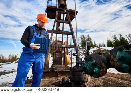 Serious Engineer In Work Overalls And Helmet Holding Clipboard And Looking At Oil Pump Rocker-machin