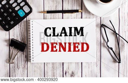Claim Denied Is Written In A White Notepad Near A Calculator, Coffee, Glasses And A Pen. Business Co