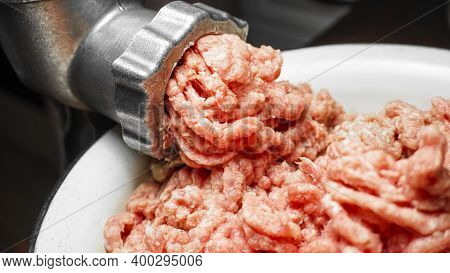 Meat Grinder In Action And Ground Beef Meat. Horizontal Close-up Color Image Of Process Of Grinding