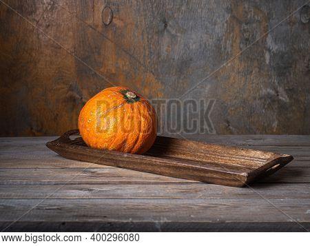 Orange Round Pumpkin On A Wooden Oblong Tray