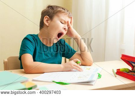 7 Yeas Old Boy Sitting At Desk And Doing Homework. Child Write Notes In Notebook, Difficult Homework