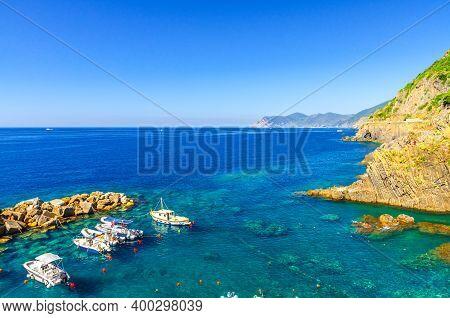Fishing Boats Moored On Water In Harbor Of Ligurian And Mediterranean Sea Near Coastline Of Riviera
