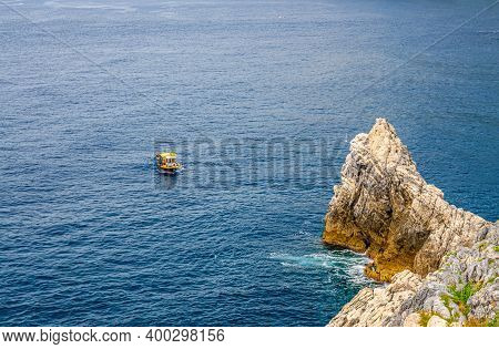 Yellow Boat On Blue Dark Water Of Grotta Di Lord Byron Near Coast With Rock Cliff, Portovenere Town,