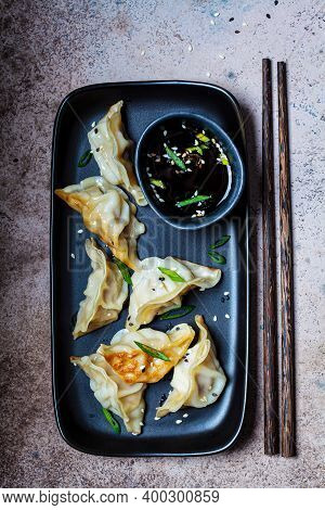 Fried Gyoza Dumplings With Sauce And Green Onions On A Black Plate, Dark Background. Japanese Cuisin