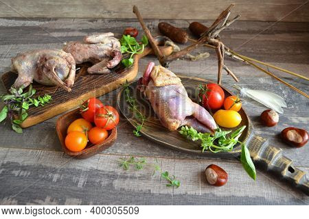 Raw Quail For Cooking On Wooden Cutting Board. Partridge And Woodcock. Hunting In Belarus