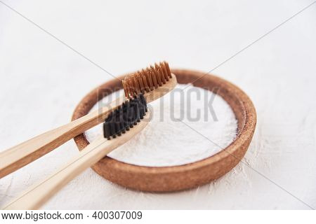 Two Wooden Bamboo Toothbrushes And Baking Soda On A White Background. Eco Friendly Toothbrushes, Zer