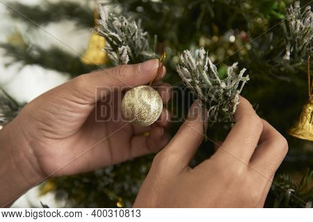 Hands Of Woman Hanging Small Bauble On Christmas Tree When Getting Ready For Celebration
