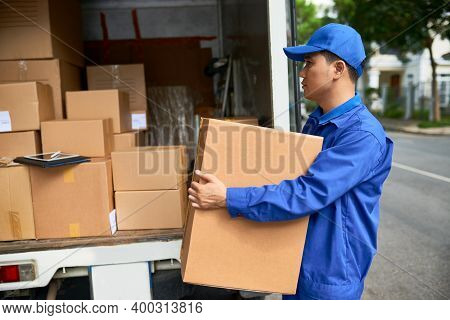 Serious Delivery Man In Blue Uniform And Cap Loading Truck With Cardbord Boxes