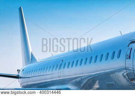 Close-up Of The Fuselage Of A White Passenger Airplane On A Clear Sunny Day