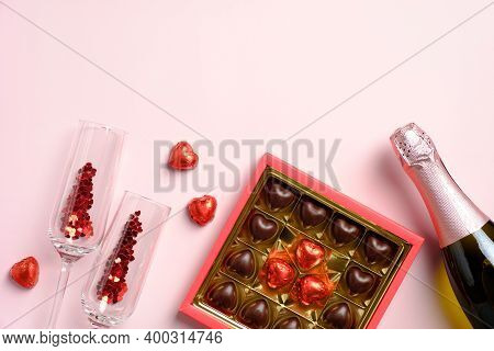 Happy Valentines Day Composition. Flat Lay, Top View Champagne Bottle, Glasses, Sweets On Pink Table