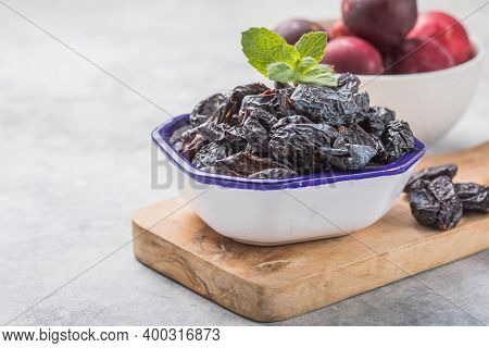 Dried Plum Or Prunus In Bowl With Fresh Plum Fruits.