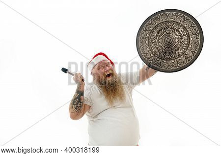 A Man Shaman With Tattooed Arms In Santa Claus Hat Looking At Shaman Tambourine, Dancing With It And