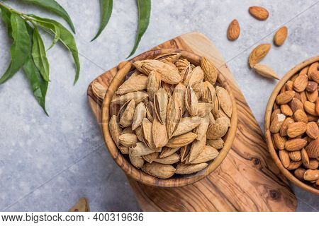 Peeled Whole Almonds And Unshelled Almonds In Bowl With Leaf. Unshelled Almonds In Bowl With Leaf. A