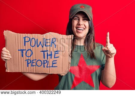 Beautiful woman wearing t-shirt with red star communist symbol asking for social movement smiling with an idea or question pointing finger with happy face, number one