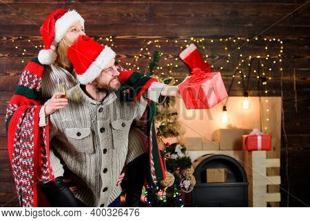 Man And Woman Santa Claus Hats Cheerful Celebrating New Year. Guy Piggybacking Girl. Celebrating Tog